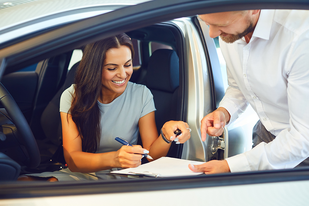 A young woman buys a car in a car showroom